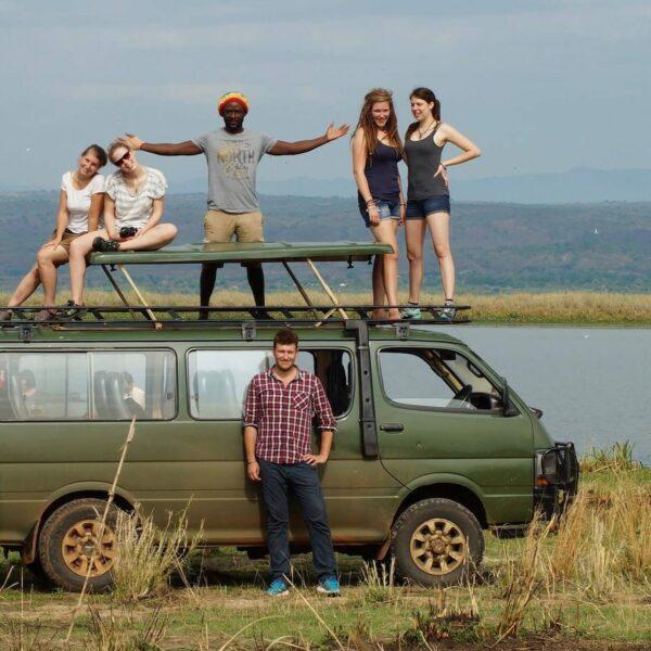 Fünf Personen stehen auf einem kleinen Bus und ein Mann steht davor